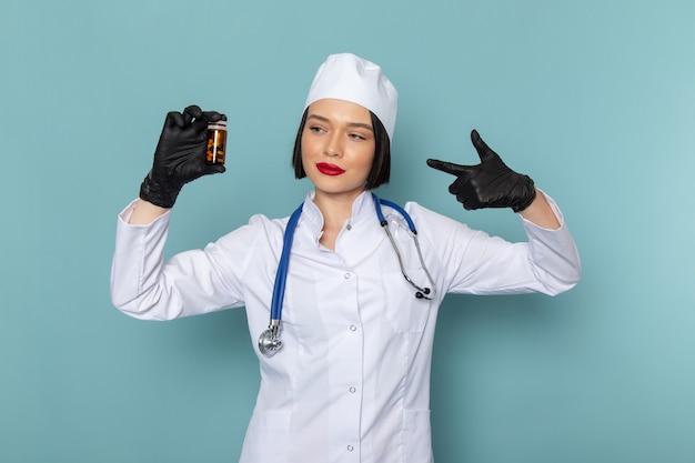 Eine junge krankenschwester der vorderansicht im weißen medizinischen anzug und im blauen stethoskop, die pillen auf dem blauen schreibtischmedizin-krankenhausarzt halten