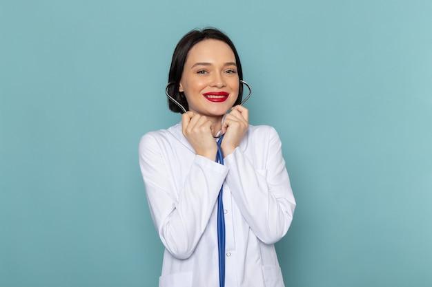 Eine junge krankenschwester der vorderansicht im weißen medizinischen anzug und im blauen stethoskop lächelnd auf dem blauen schreibtischmedizinkrankenhausarzt