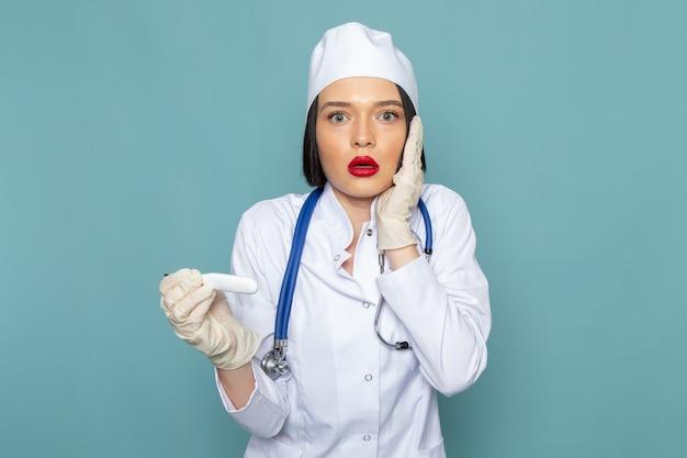 Eine junge krankenschwester der vorderansicht im weißen medizinischen anzug und im blauen stethoskop mit überraschtem ausdruck auf dem blauen arztanzug des medizinischen krankenhauses