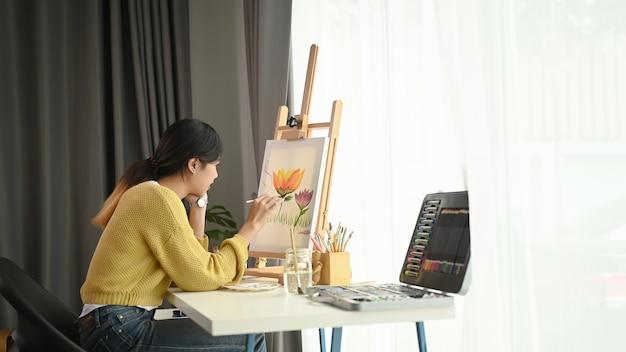 Eine junge künstlerin, die zu hause kreativ malt, während sie an ihrem arbeitsbereich sitzt
