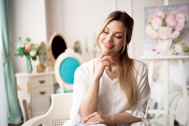 Eine junge künstlerin mit einem bild auf einer staffelei zu hause. der maler malt ölgemälde.