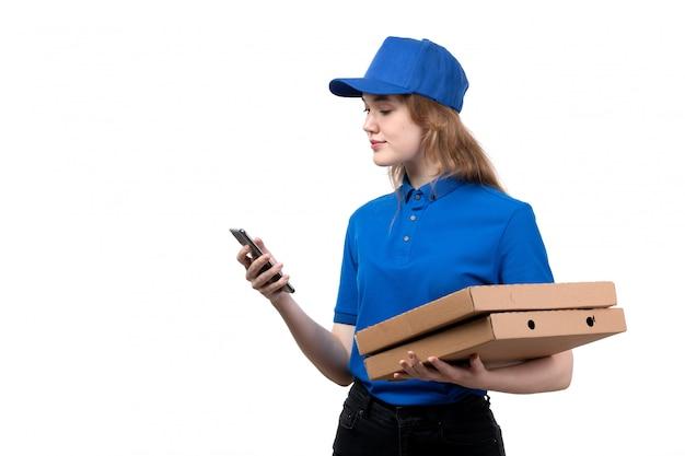 Eine junge kurierin der vorderansicht, eine weibliche arbeiterin des lebensmittellieferservices, die lebensmittelpakete hält und ein telefon mit einem lächeln auf weiß verwendet