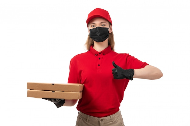 Eine junge kurierin der vorderansicht in den roten handschuhen der roten kappe der roten kappe und der schwarzen maske, die pizzaschachteln hält
