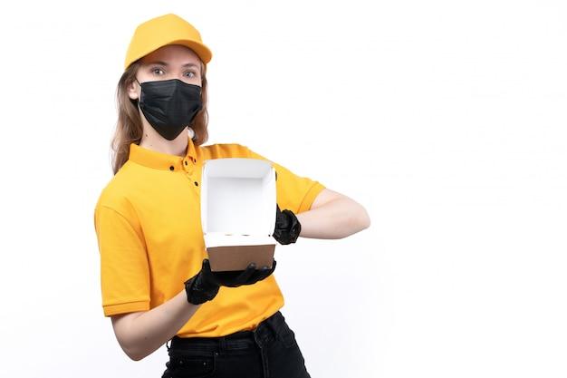 Eine junge kurierin der vorderansicht in den schwarzen handschuhen der gelben uniform und der schwarzen maske, die eine leere lebensmittelverpackung hält