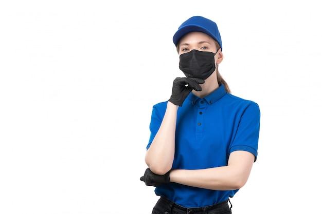 Eine junge kurierin der vorderansicht in den schwarzen schwarzen handschuhen der blauen uniform und der schwarzen maske