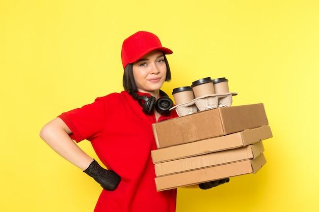 Eine junge kurierin der vorderansicht in den schwarzen schwarzen handschuhen der roten uniform und der roten kappe, die nahrungsmittelkästen und kaffeetassen hält