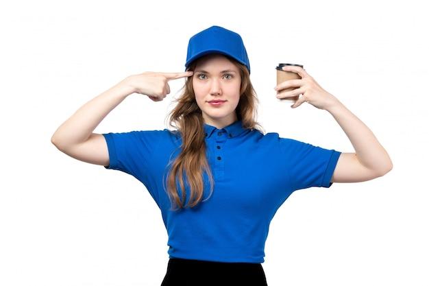 Eine junge kurierin der vorderansicht in der blauen kappe des blauen hemdes und in der schwarzen hose, die kaffeetasse hält, die auf ihren kopf auf weiß zeigt