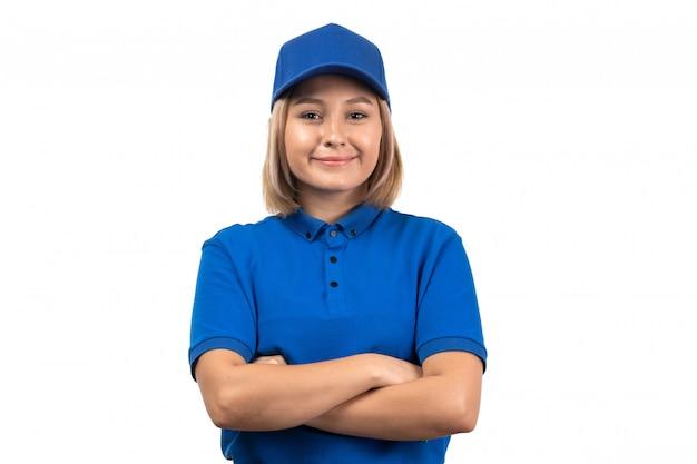 Eine junge kurierin der vorderansicht in der blauen uniform, die gerade mit lächeln auf ihrem gesicht aufwirft