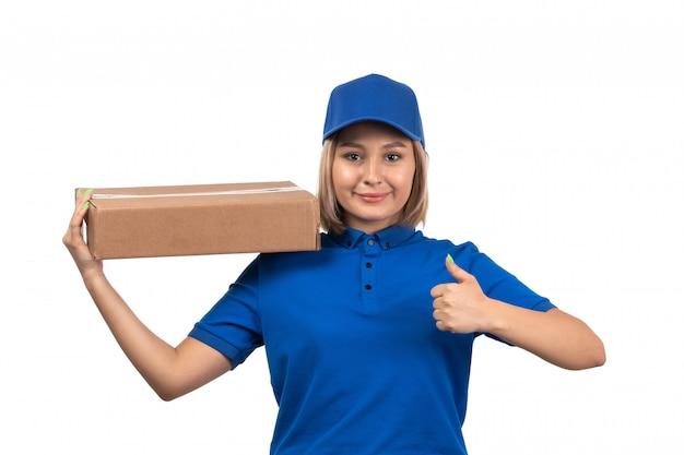 Eine junge kurierin der vorderansicht in der blauen uniform, die lebensmittel-lieferpaket mit lächeln auf ihrem gesicht hält