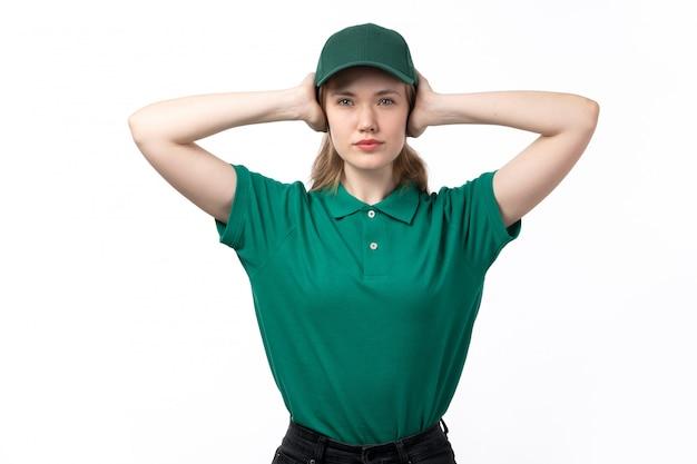 Eine junge kurierin der vorderansicht in der grünen uniform, die ihre ohren bedeckt, die auf weiß aufwerfen