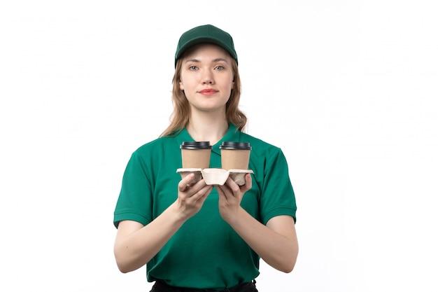 Eine junge kurierin der vorderansicht in der grünen uniform, die kaffeetassen der lieferung hält