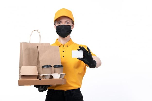 Eine junge kurierin der vorderansicht in gelben schwarzen handschuhen der uniform und der schwarzen maske, die kaffeetassen und lebensmittelverpackungen hält