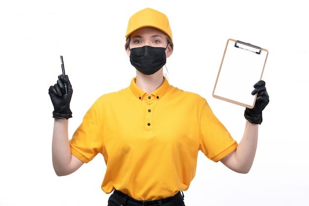 Eine junge kurierin der vorderansicht in gelben schwarzen handschuhen der uniform und der schwarzen maske, die notizblock hält