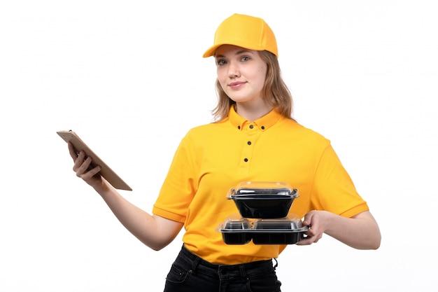 Eine junge kurierin der vorderansicht weiblicher arbeiter des lebensmittel-lieferservice lächelnd, der notizblock für unterschriften und schalen mit essen auf weiß hält