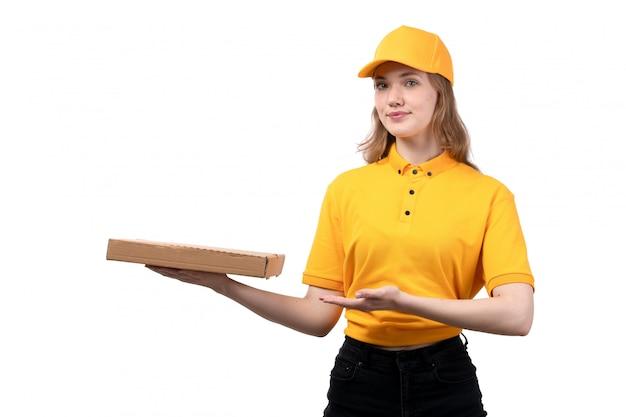 Eine junge kurierin der vorderansicht weiblicher arbeiter des lebensmittel-lieferservices lächelnd, der lieferkasten auf weiß hält