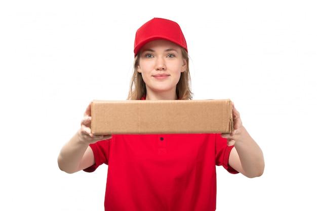 Eine junge kurierin der vorderansicht weiblicher arbeiter des lebensmittel-lieferservices lächelnde haltebox mit essen auf weiß