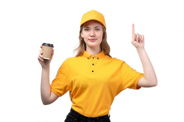 Eine junge kurierin der vorderansicht weiblicher arbeiter des lebensmittellieferservice lächelnd, der eine kaffeetasse mit erhöhtem finger auf weiß hält
