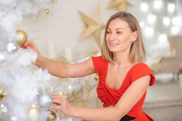 Eine junge lächelnde frau bereitet einen weihnachtsbaum für den urlaub vor.