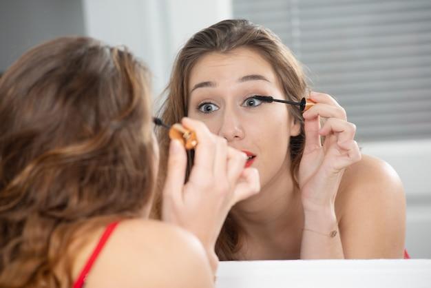 Eine junge lächelnde frau, die make-up in den spiegel einsetzt