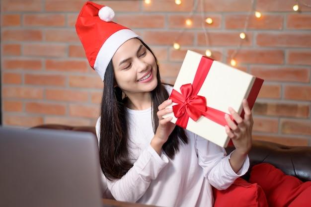 Eine junge lächelnde frau, die roten weihnachtsmannhut trägt, der videoanruf auf sozialem netzwerk mit familie und freunden am weihnachtstag macht.