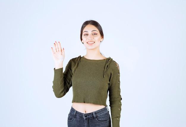 Eine junge lächelnde frau im grünen pullover, die eine hand winkt.