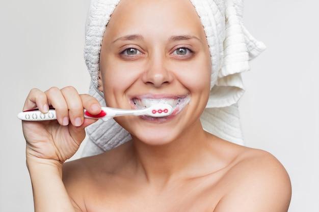 Eine junge lächelnde frau mit einem weißen handtuch auf dem kopf, die ihre zähne mit einer zahnbürste putzt
