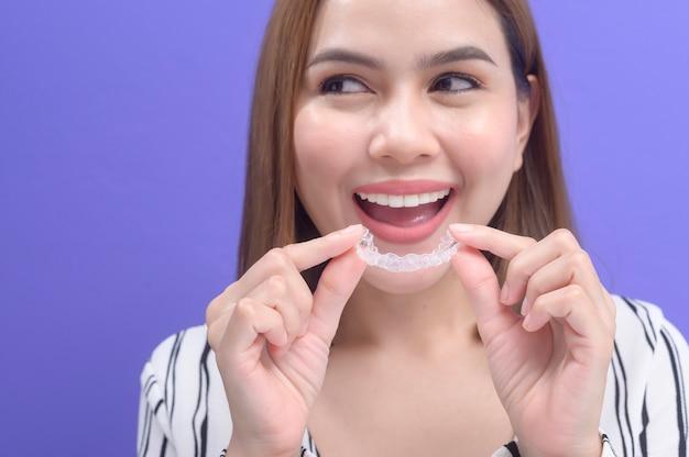 Eine junge lächelnde frau mit invisalign-klammern im studio, zahnmedizin und kieferorthopädisches konzept.