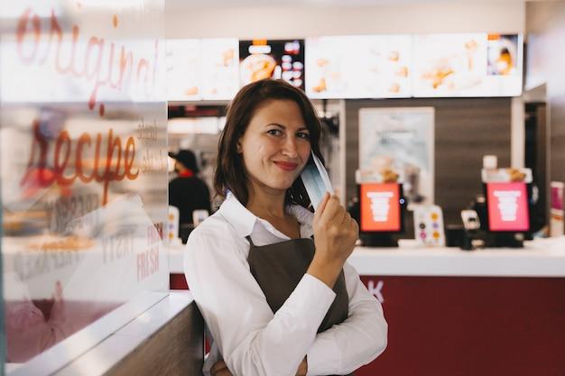 Eine junge lächelnde geschäftsfrau in einer schürze steht in einem café vor einem schaufenster, ihre arme verschränkt und schaut in die kamera.