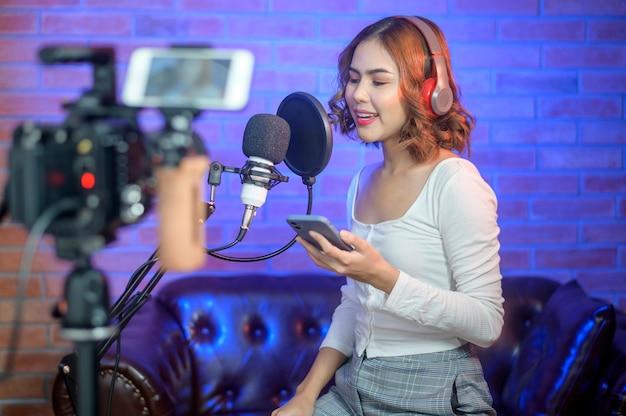 Eine junge lächelnde sängerin, die kopfhörer mit einem mikrofon trägt, während sie ein lied in einem musikstudio mit bunten lichtern aufnimmt.