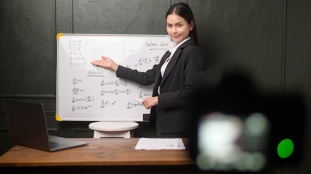 Eine junge lehrerin verwendet eine kamera zum aufzeichnen von online-lektionen während der quarantäne, online-bildung und fernunterricht.