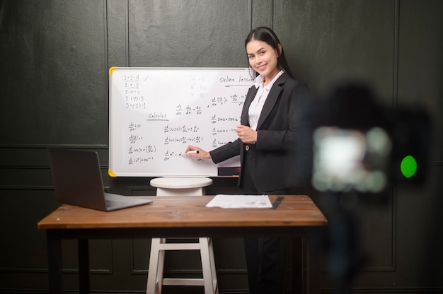Eine junge lehrerin verwendet eine kamera zum aufzeichnen von online-lektionen während der quarantäne, online-bildung und fernunterricht