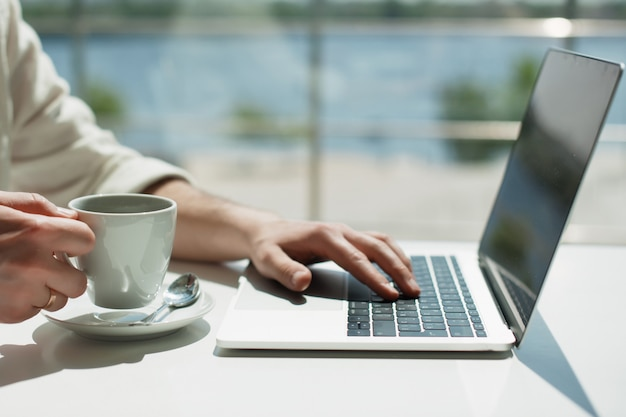 Eine junge männliche jahrtausendwende arbeitet fern auf einem laptop.