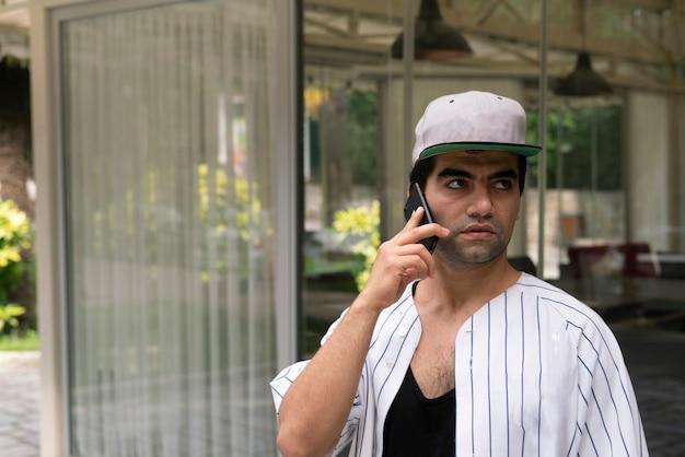 Eine junge männliche person, die ein smartphone hält und draußen auf der straße telefoniert