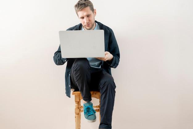Eine junge männliche person, die zu hause mit laptop arbeitet, online-freiberufler-lifestyle, der in der nähe der wand isoliert sitzt sitting