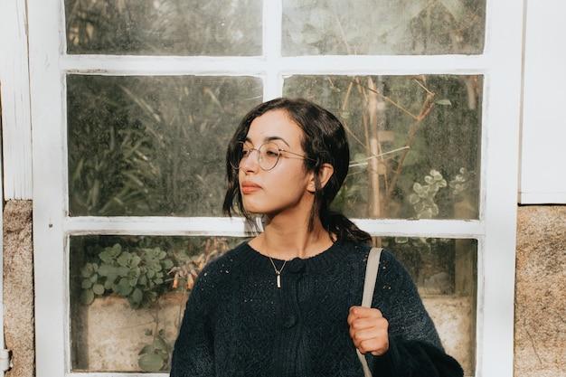 Eine junge marokkanische frau vor einem weißen hölzernen kristallfenster