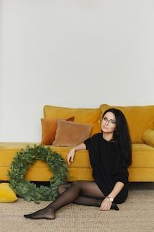 Eine junge modelfrau in einem schwarzen strickkleid sitzt in der nähe der gelben couch mit einem weihnachtskranz in einem minimalistischen interieur.