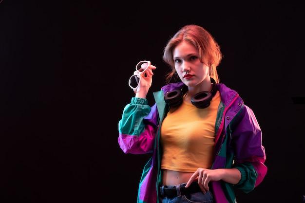 Eine junge moderne dame der vorderansicht im bunten mantelorangen-t-shirt mit schwarzen kopfhörern und sonnenbrillen, die aufwerfen