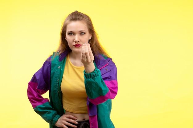 Eine junge moderne frau der vorderansicht in der schwarzen hose des gelben hemdes und der bunten jacke, die fragen stellt