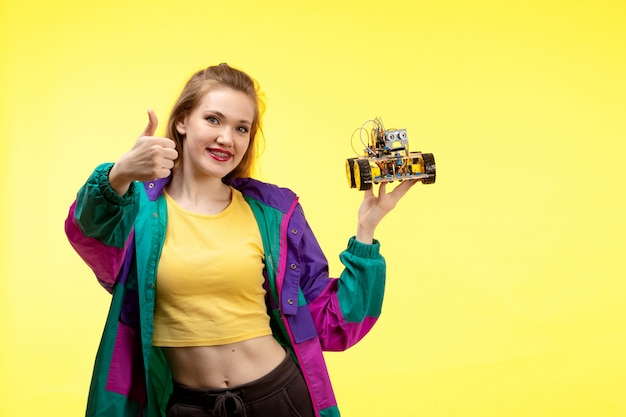 Eine junge moderne frau der vorderansicht in der schwarzen hose des gelben hemdes und der bunten jacke, die spielzeugauto hält, das glücklichen ausdruck aufwirft