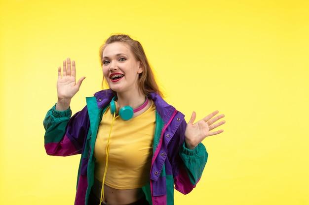 Eine junge moderne frau der vorderansicht in der schwarzen hose des gelben hemdes und der bunten jacke mit farbigen kopfhörern, die glücklichen ausdruck aufwerfen