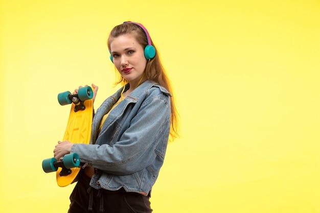 Eine junge moderne frau der vorderansicht in der schwarzen hose des gelben hemdes und im jeansmantel, der skateboard mit farbigen kopfhörern hält, die aufwerfen