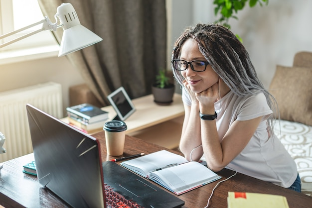 Eine junge moderne frau kommuniziert mit freunden über einen videolink online zu hause in einem raum mit einem laptop
