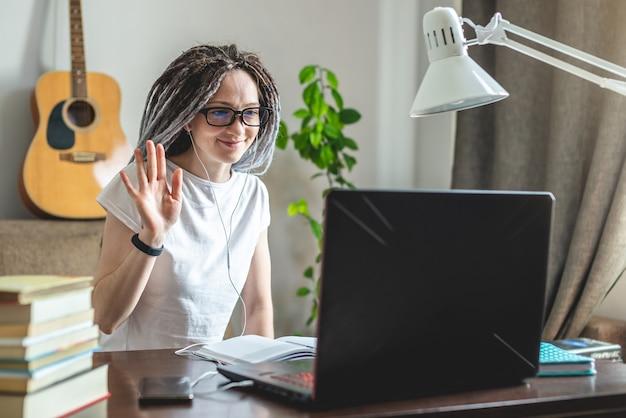Eine junge moderne frau winkt freunden zu, die per videolink mit freunden zu hause in einem raum mit einem laptop online hallo sagen