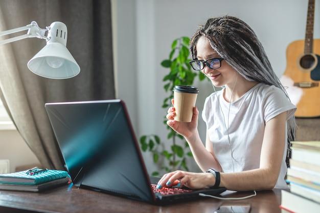 Eine junge moderne mitarbeiterin arbeitet online zu hause in einem raum mit einem laptop