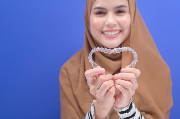 Eine junge muslimische frau mit invisalign-klammern im studio, in der zahnmedizin und im kieferorthopädischen konzept.