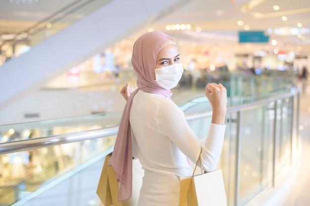 Eine junge muslimische frau mit schutzmaske im einkaufszentrum