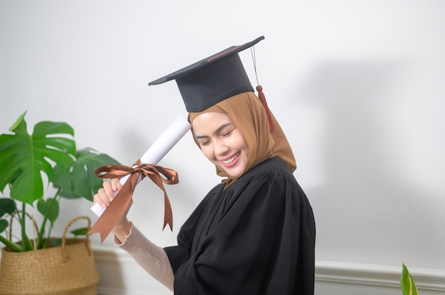 Eine junge muslimische frau schloss ihr studium mit einem zertifikat ab.