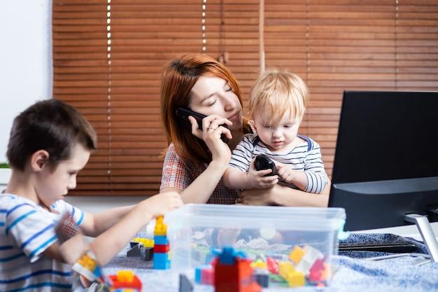 Eine junge mutter, die am telefon spricht und versucht, an einem computer an einem fernarbeits-weichzeichner zu arbeiten. von zuhause aus arbeiten