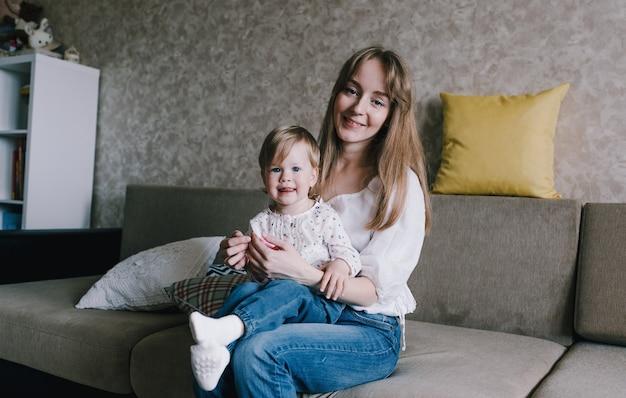 Eine junge mutter hält ihr kleines mädchen in den armen und spielt mit ihr, sitzt zu hause auf der couch, genießt die mutterschaft und hat spaß. das konzept des familienglücks