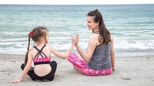 Eine junge mutter mit einer kleinen tochter in sportbekleidung sitzt am strand